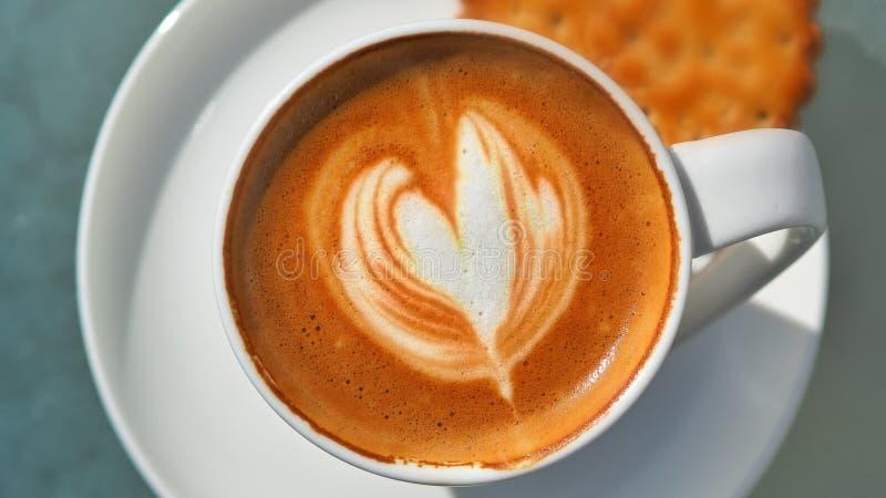 Corazoncaffee med tefatet I mj?lka kaffeskum, kaffeskum, artfully som en hj?rta trollades arkivfoto
