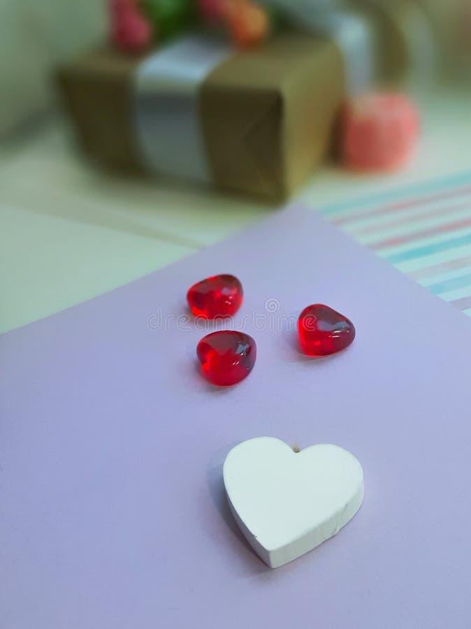 Corazones blancos y rojos delante de la caja de regalo en fondo del papel de la lavanda foto de archivo