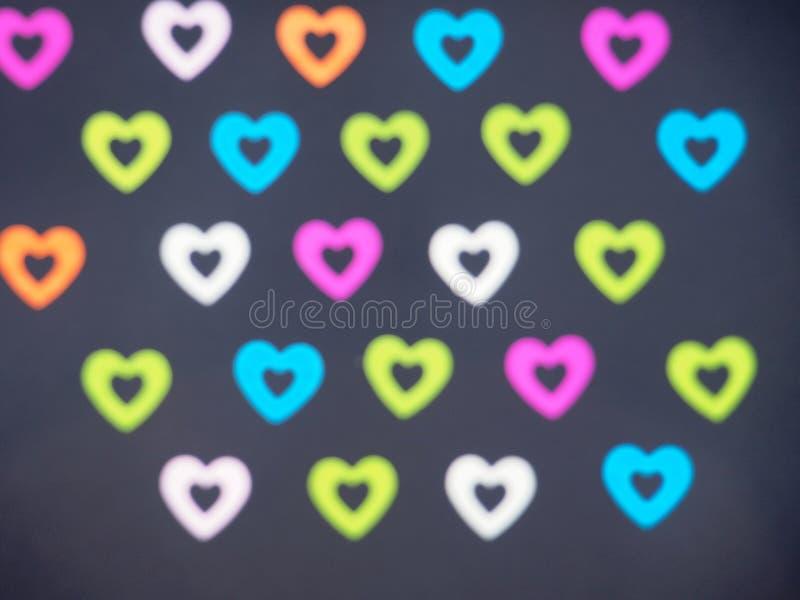 Corazones brillantes coloridos en un fondo negro Se arreglan los corazones imagenes de archivo