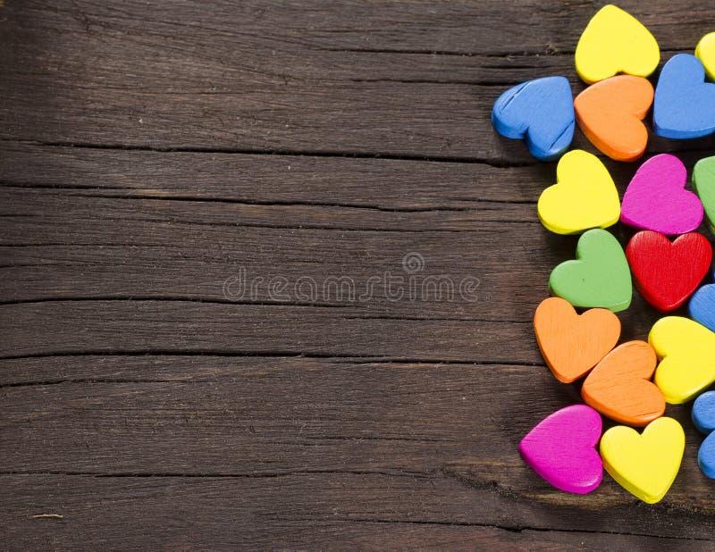 Corazones coloridos en fondo de madera. imagen de archivo