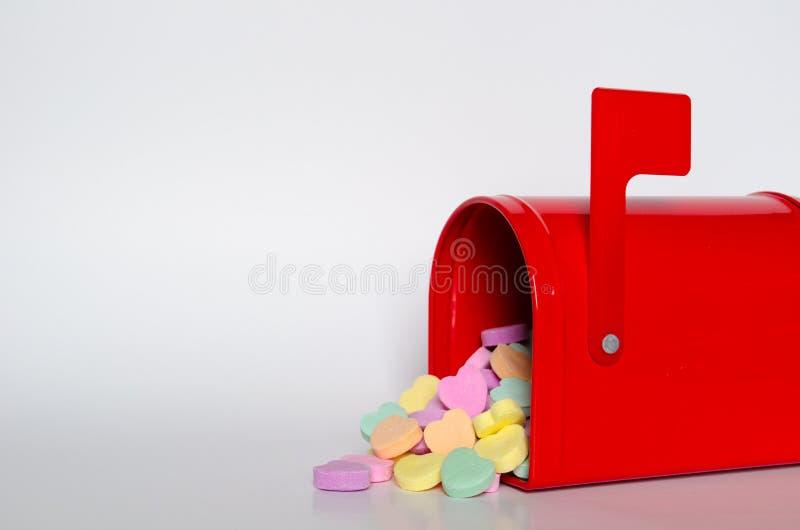 Corazones de la conversación del caramelo que se derraman fuera de un buzón rojo imágenes de archivo libres de regalías