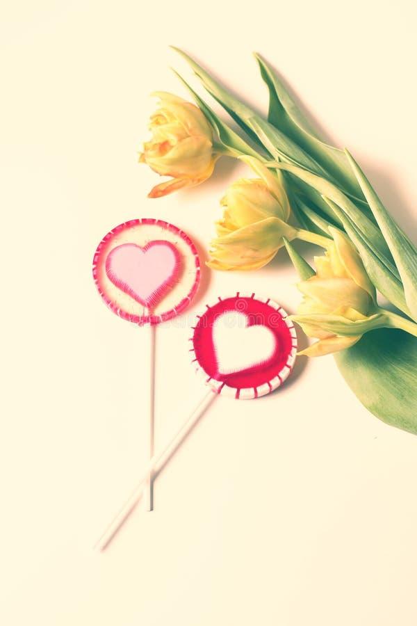 Corazones de la piruleta y tulipanes hermosos en el fondo blanco fotos de archivo