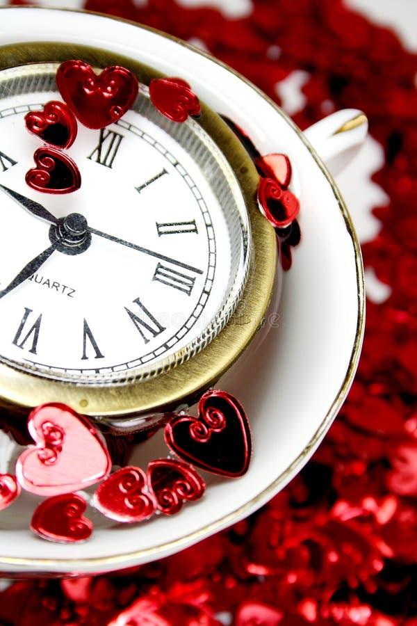 Corazones de la St-Tarjeta del día de San Valentín con el reloj en una taza imagenes de archivo