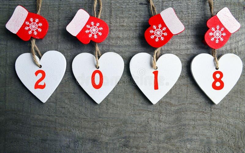 Corazones de madera blancos decorativos de la Navidad y manoplas rojas con 2018 números en fondo de madera con el espacio de la c foto de archivo