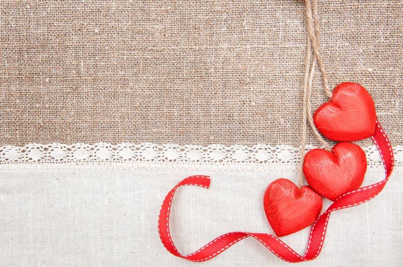 Corazones de madera, cinta y paño de lino en la arpillera fotografía de archivo