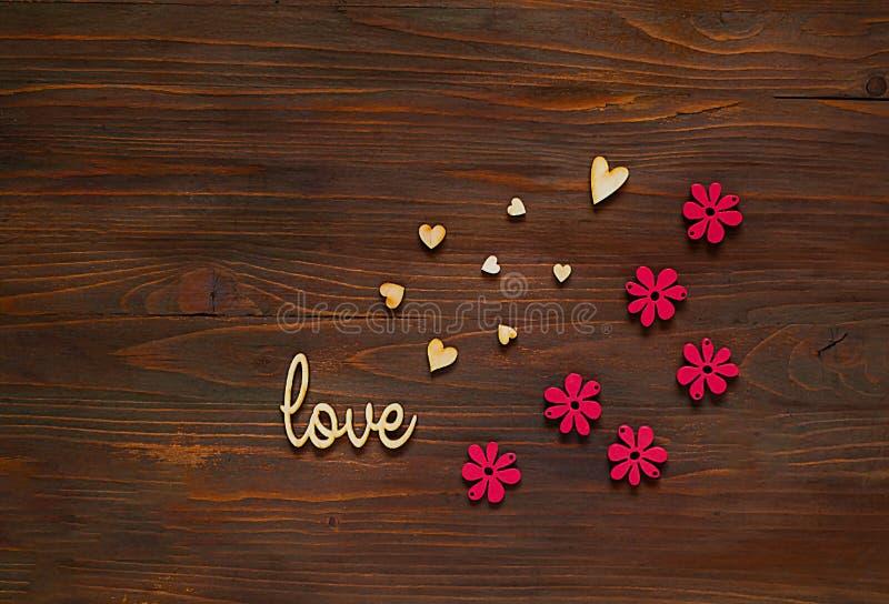 Corazones de madera con amor de la inscripción y la decoración de flores en un fondo de madera, concepto de composición festiva,  imagenes de archivo