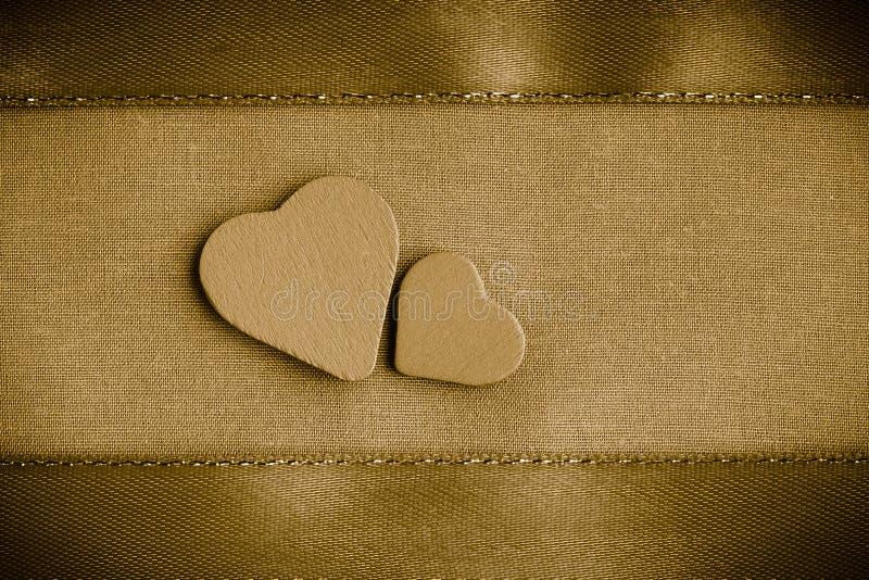 Corazones decorativos de madera de la tarjeta del día de San Valentín en fondo de oro del paño imágenes de archivo libres de regalías