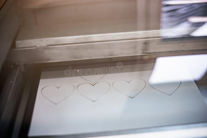 Corazones del corte de máquina de grabado del laser del papel imagenes de archivo