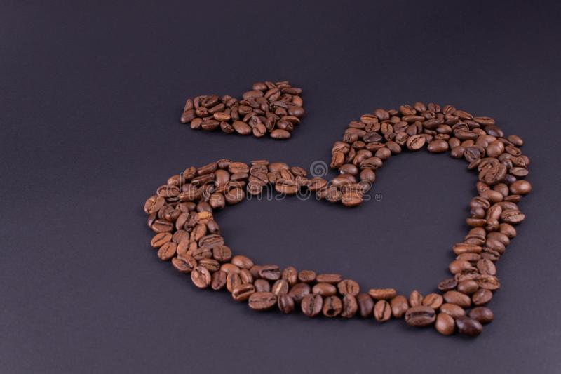 Corazones grandes y pequeños del café en la esquina inferior derecha en un fondo oscuro fotografía de archivo libre de regalías