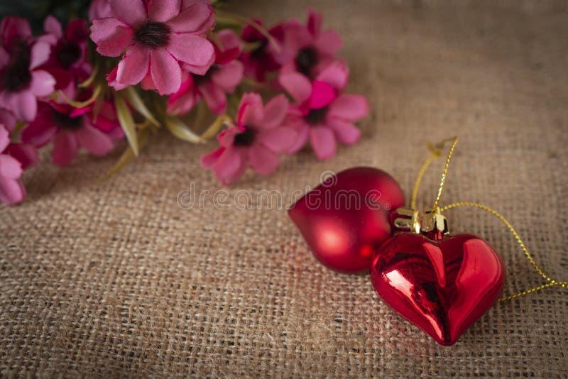 Corazones plásticos rojos puestos en el saco Hay una flor colocada en la parte posterior izquierda fotografía de archivo libre de regalías