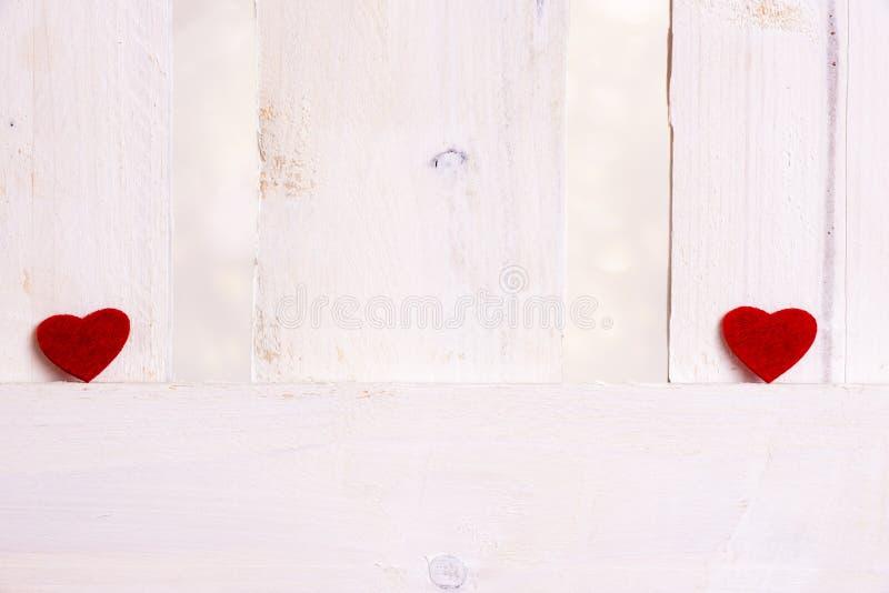 Corazones rojos aparte en una cerca blanca fotos de archivo libres de regalías