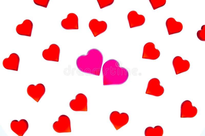 Corazones rojos brillantes en un fondo rayado con dos corazones rosados Para utilizar día del ` s de la tarjeta del día de San Va fotografía de archivo libre de regalías
