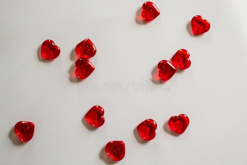 Corazones rojos claros en el fondo blanco para el día de tarjeta del día de San Valentín imagenes de archivo