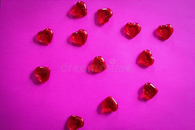 Corazones rojos claros en el fondo rosado para el día de tarjeta del día de San Valentín imagenes de archivo