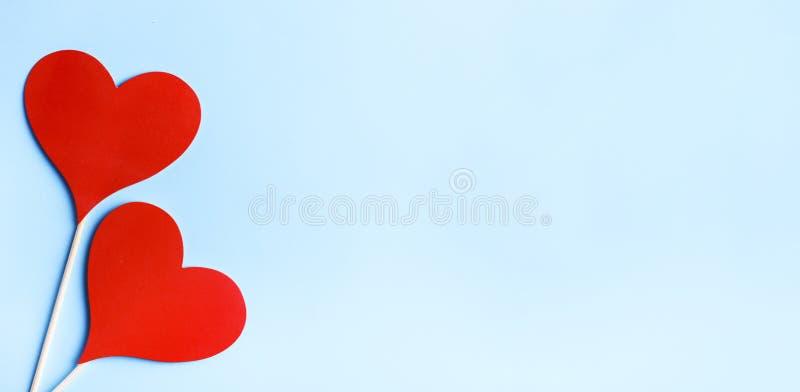 Corazones rojos de la tarjeta del día de San Valentín en fondo azul en colores pastel desde arriba fotografía de archivo