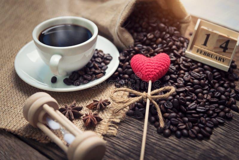 Corazones rojos del brillo en los granos de café foto de archivo