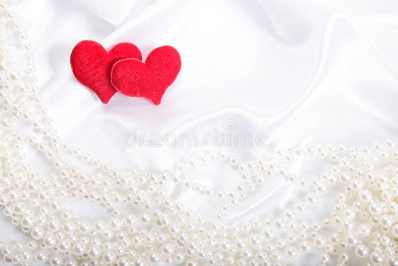 Corazones rojos en fondo de las perlas fotografía de archivo
