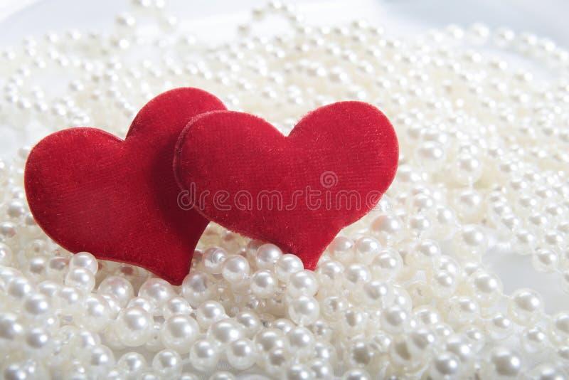 Corazones rojos en fondo de las perlas imagen de archivo libre de regalías