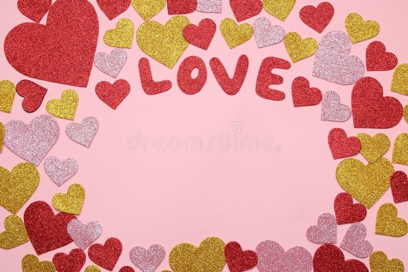 Corazones y amor brillantes multicolores del texto en un fondo rosado brillante marco de corazones, visión superior con el espaci imágenes de archivo libres de regalías