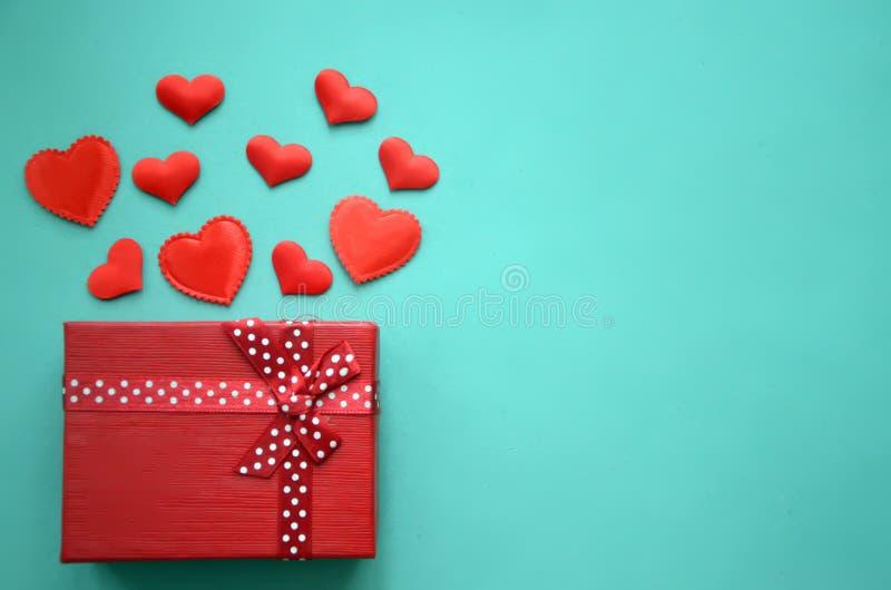 Corazones y caja de regalo rojos en un fondo foto de archivo