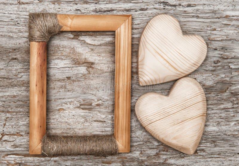 Corazones y marco de madera en la madera vieja imagenes de archivo