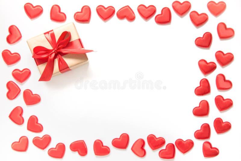 Corazones y regalo rojos con la cinta roja en blanco Visión superior Tarjeta del `s de la tarjeta del día de San Valentín imágenes de archivo libres de regalías