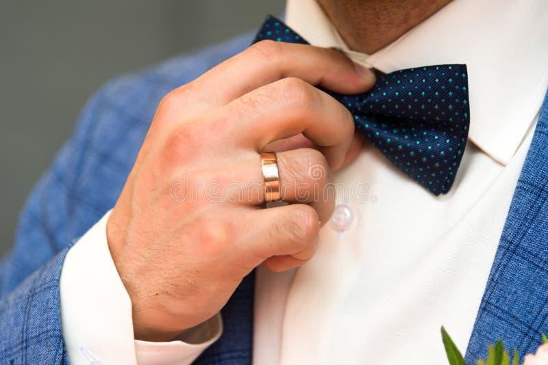 Corbata de lazo azul en las manos del novio clo foto de archivo