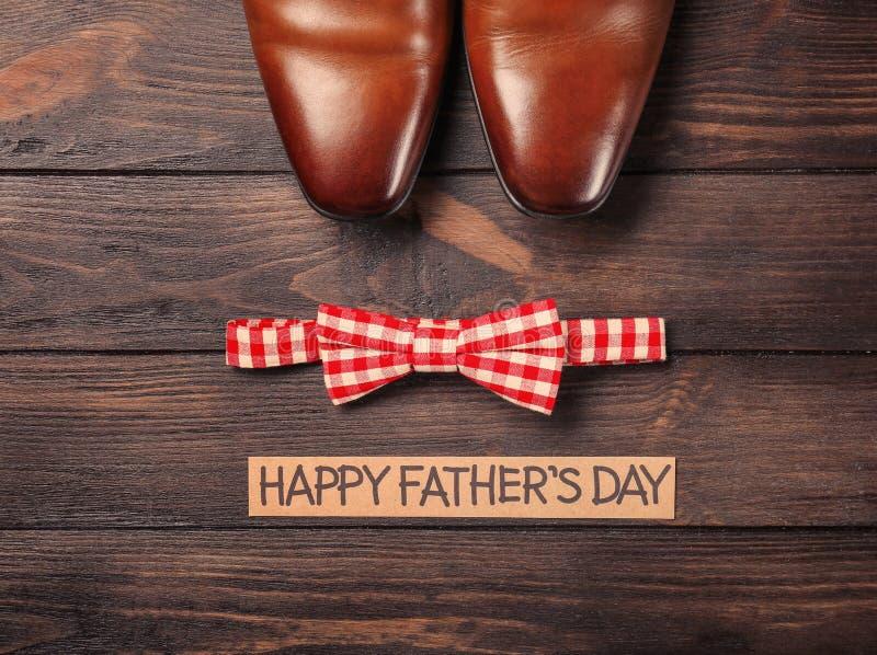 Corbata de lazo y pares de zapatos masculinos en fondo de madera imagenes de archivo