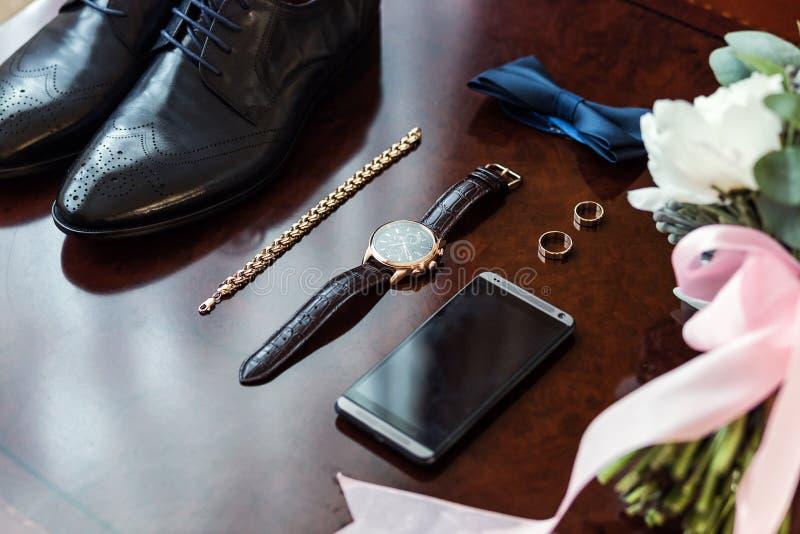 Corbata de lazo, zapatos, anillos de bodas, teléfono, reloj, ramo del ` s de la novia, imagenes de archivo