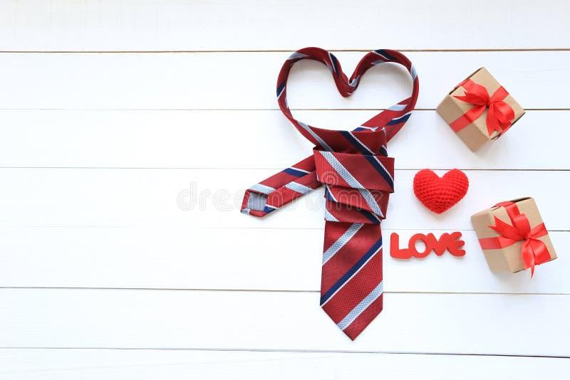 Corbata del corazón y caja de regalo roja con la cinta roja y corazón hecho a mano del ganchillo en el fondo de madera para el dí fotos de archivo libres de regalías