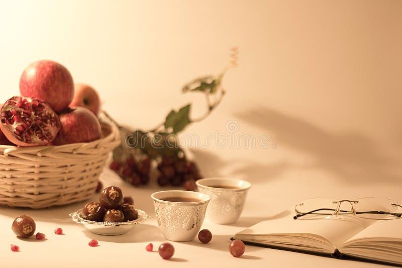Corbeille de fruits, dates sur une cuvette argentée, tasses de thé Arabes avec le livre ouvert et verres de lecture photo libre de droits