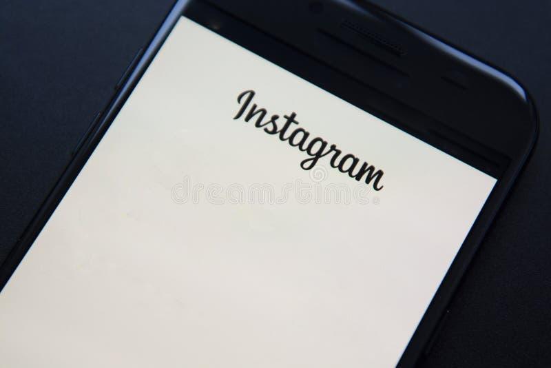 Corby, Великобритания - 27-ое января 2019: Смартфон с применением Instagram на экране Темная, черная предпосылка Белая страница стоковое фото