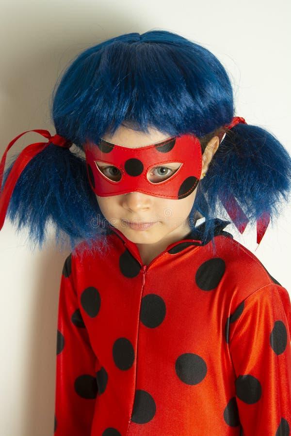 E 12-ое марта 2019 - маленькая девочка в костюме Myraculous Ladybug cosplay Ladybug супергероя с голубой хворостиной, стоковые фотографии rf