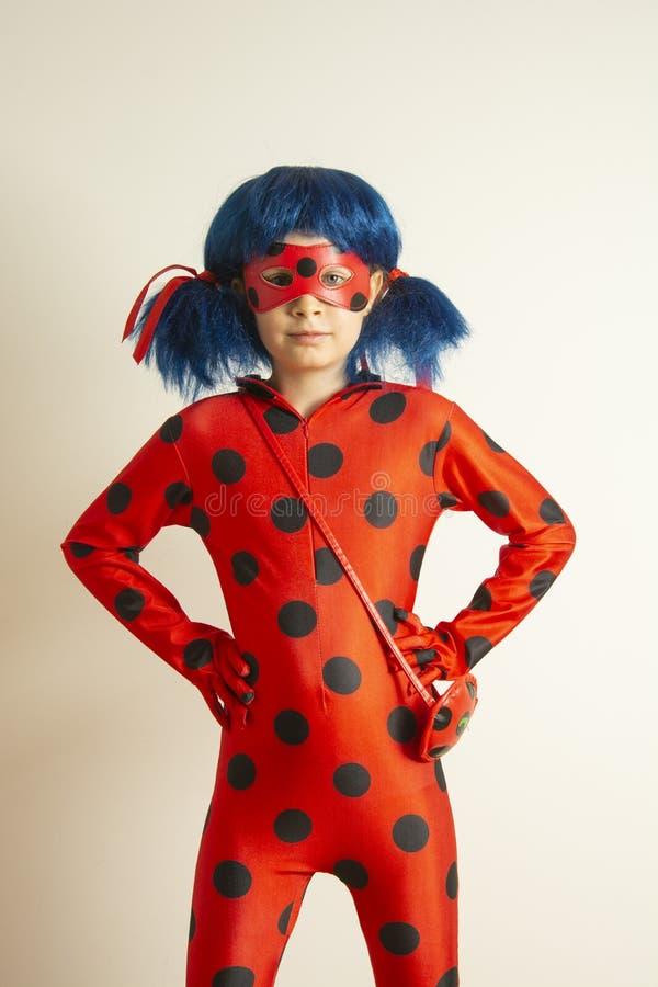 Corby, Reino Unido 12 de mar?o de 2019 - menina no traje cosplay de Myraculous do joaninha Joaninha do super-her?i com galho azul fotos de stock
