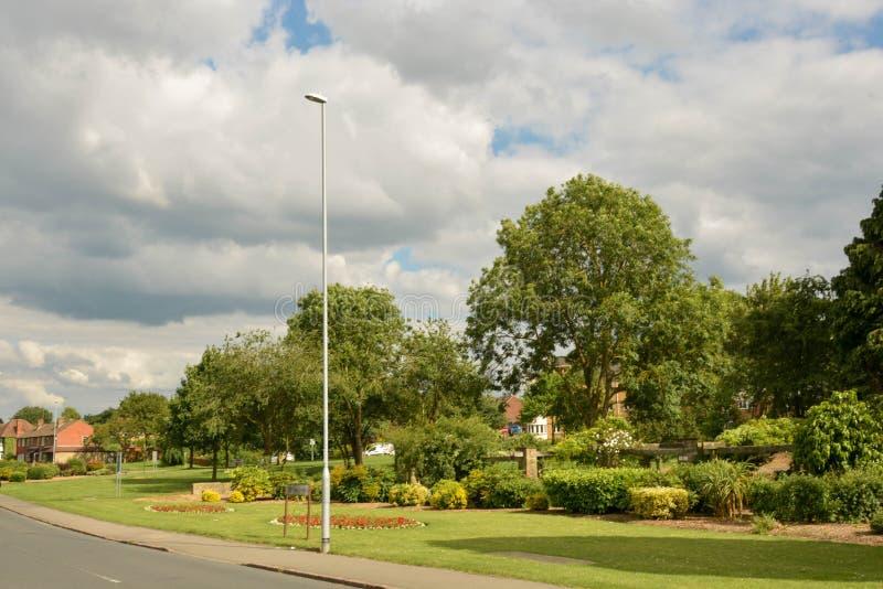 Corby?U K,June2,2019年-道路风景看法穿过一个美丽的绿色叶茂盛公园庭院和路 库存照片