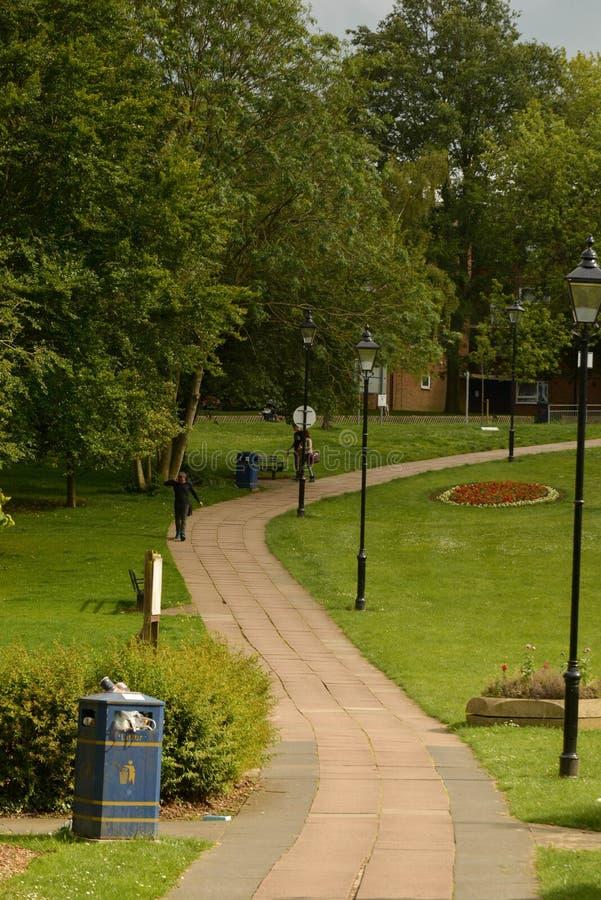Corby, u K, June2, 2019 - сценарный взгляд пути через красивый зеленый густолиственный сад парка и дорога стоковая фотография rf