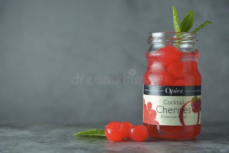 Corby, U.K., June 29, 2019 - Opies cocktail cherries in glass jr bottle, on dark background stock images