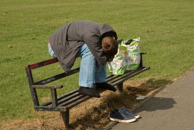 Corby U K , Juni 20, 2019 - hemlös man som utanför sover på en bänk fotografering för bildbyråer