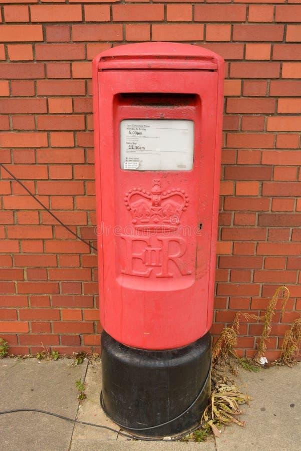 Corby U K , Juni 20, 2019 - traditionell brittisk röd postbox nära tegelstenväggen arkivfoto