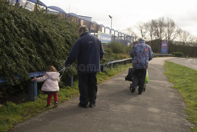 Corby, U K, 19 Maart 2019 - Grootouders die met hun meisjesneef lopen, die van elkaar & x27 genieten; s bedrijf Pensioenpaar stock afbeelding