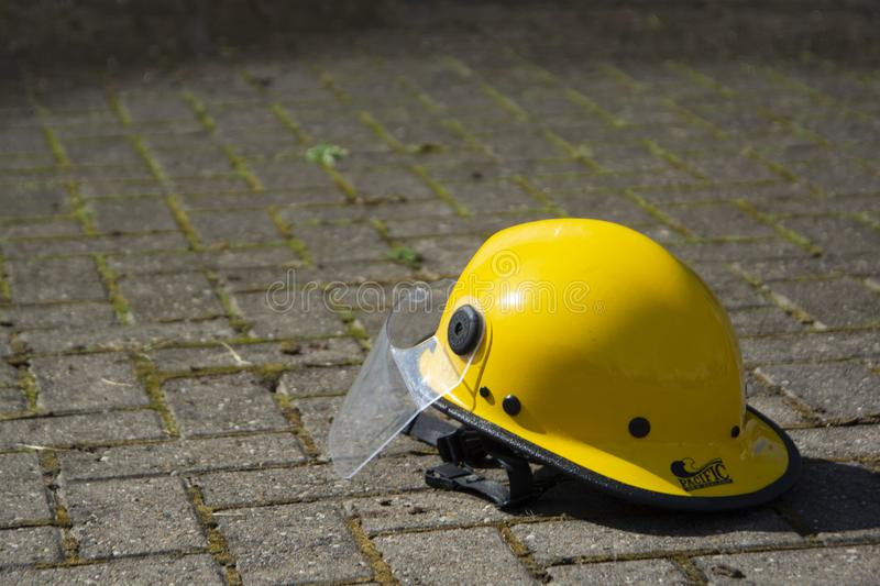 Corby, U.K. September 13, 2019 - one yellow helmet on the ground at British fire engine open day family event at fire station in. Corby, rescue, firefighter royalty free stock image