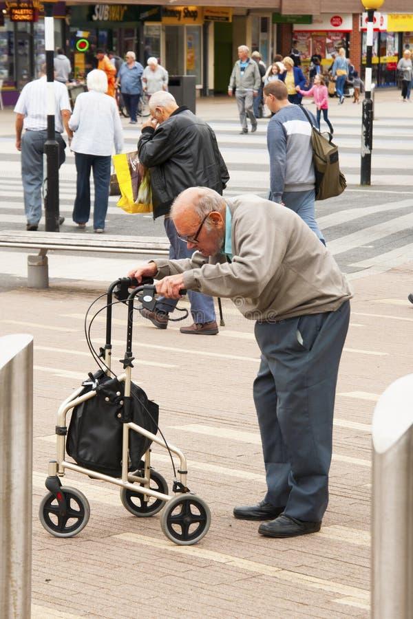 Corby, Vereinigtes Königreich - 28. August 2018: Ein alter Mann, der Mobilitätshilfsdas stehende gehende Basieren auf Wandererbeg lizenzfreie stockfotografie