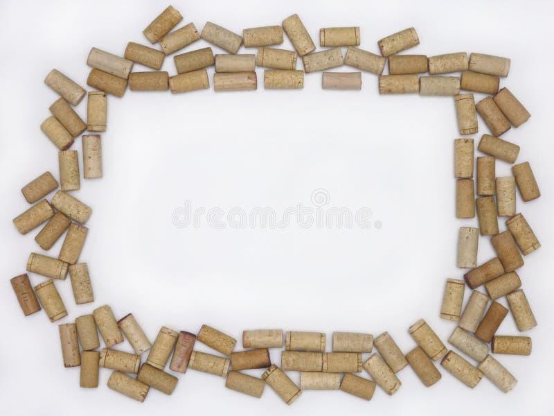 Corchos en blanco del vino que crean un marco contra un fondo blanco imágenes de archivo libres de regalías