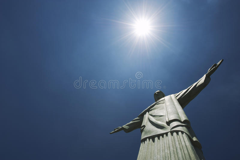 Corcovado Christ the Redeemer Rio de Janeiro Brazil Sun. Statue of Christ the Redeemer at Corcovado Mountain standing under bright sun against blue sky stock photo