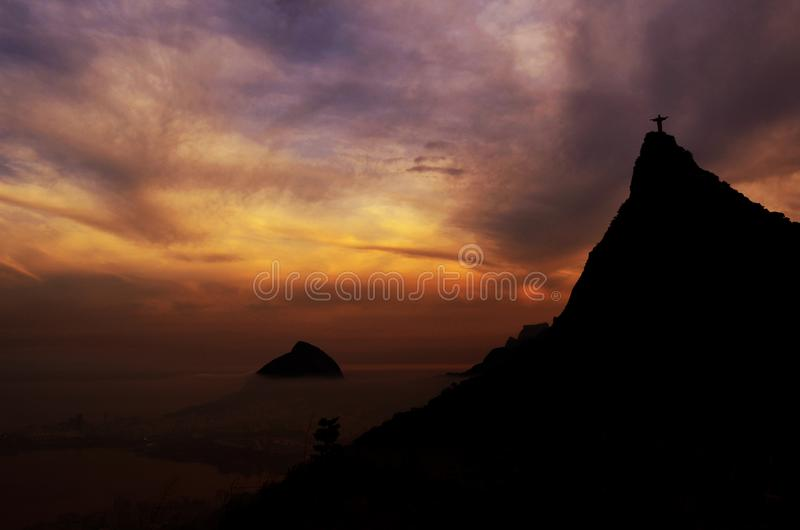Corcovado mountain Christ the Redeemer standing in golden sunset clouds Rio de Janeiro Brazil. stock photos
