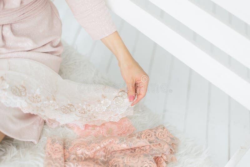 Cordón en las manos del amo La costurera sostiene la tela en sus manos y hace la colocación imágenes de archivo libres de regalías
