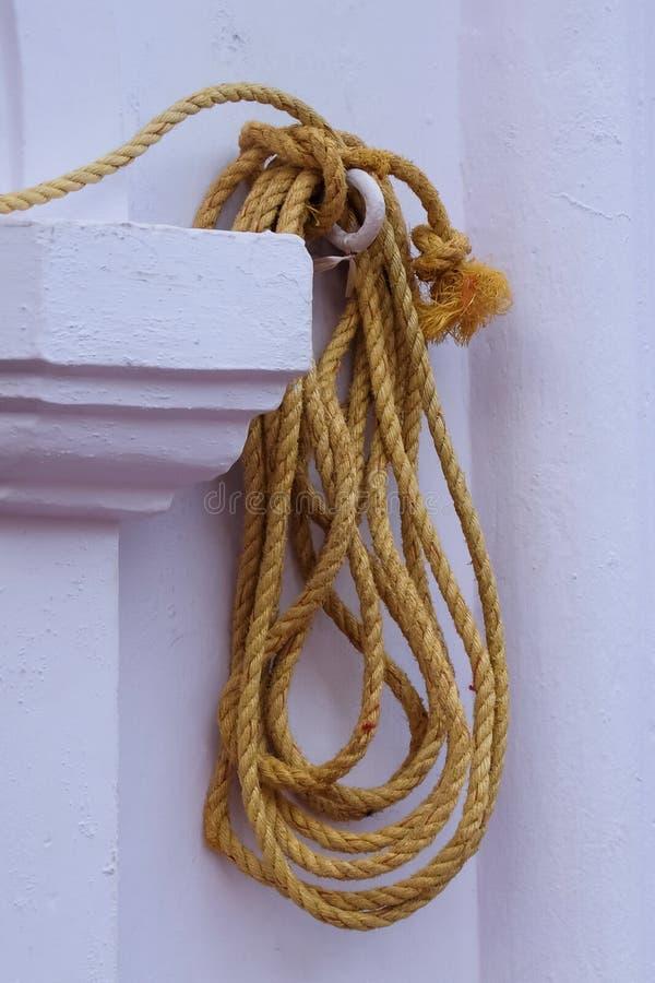Corda amarela que pendura na parede fotografia de stock