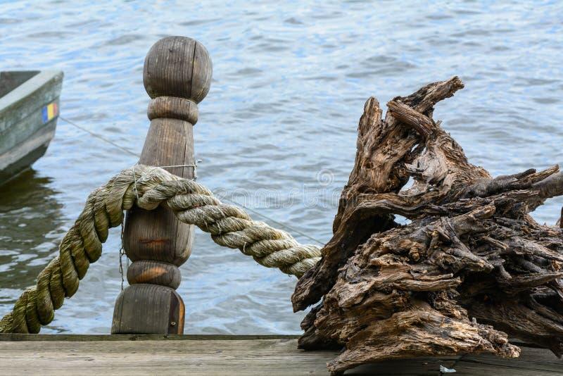 Corda atada ao longo de um poste de amarração do navio Docas com corda no porto, bl fotografia de stock