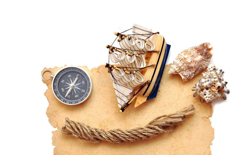 Corda, bussola e barca classica di modello su vecchio documento fotografia stock