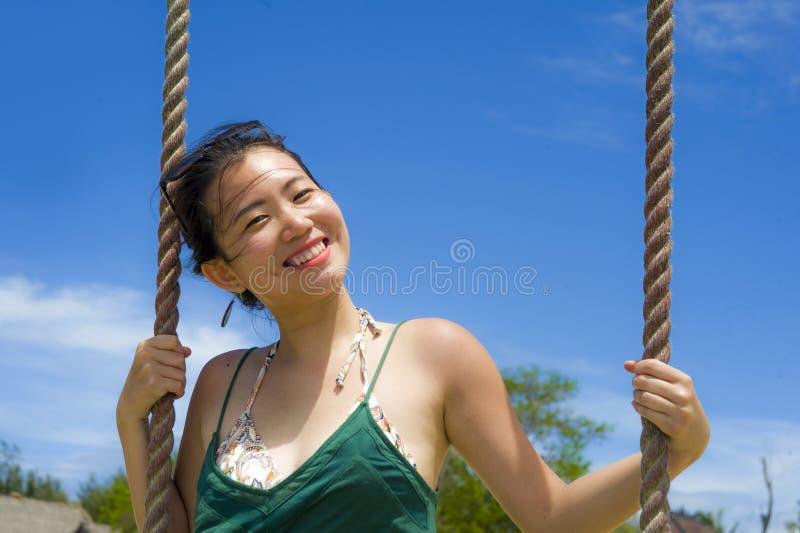 Corda chinesa asiática feliz do balanço da terra arrendada da mulher que tem o divertimento em um sorriso do céu azul do verão po foto de stock